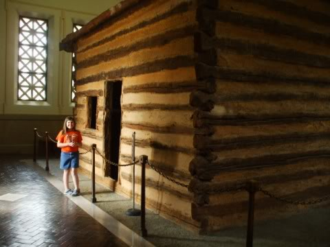Kayla standing in front of the replica cabin