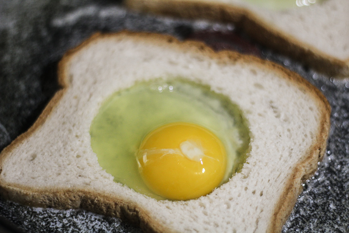 placing egg in the center of the toast for egg in the hole