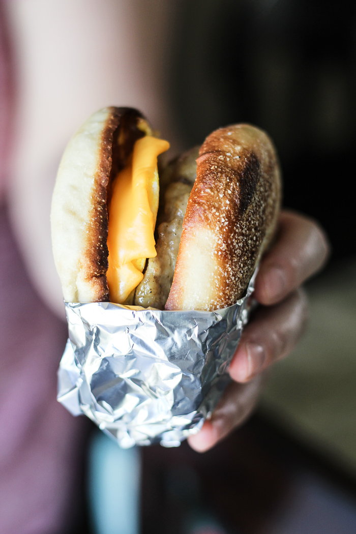 holding breakfast sandwich wrapped in aluminum foil