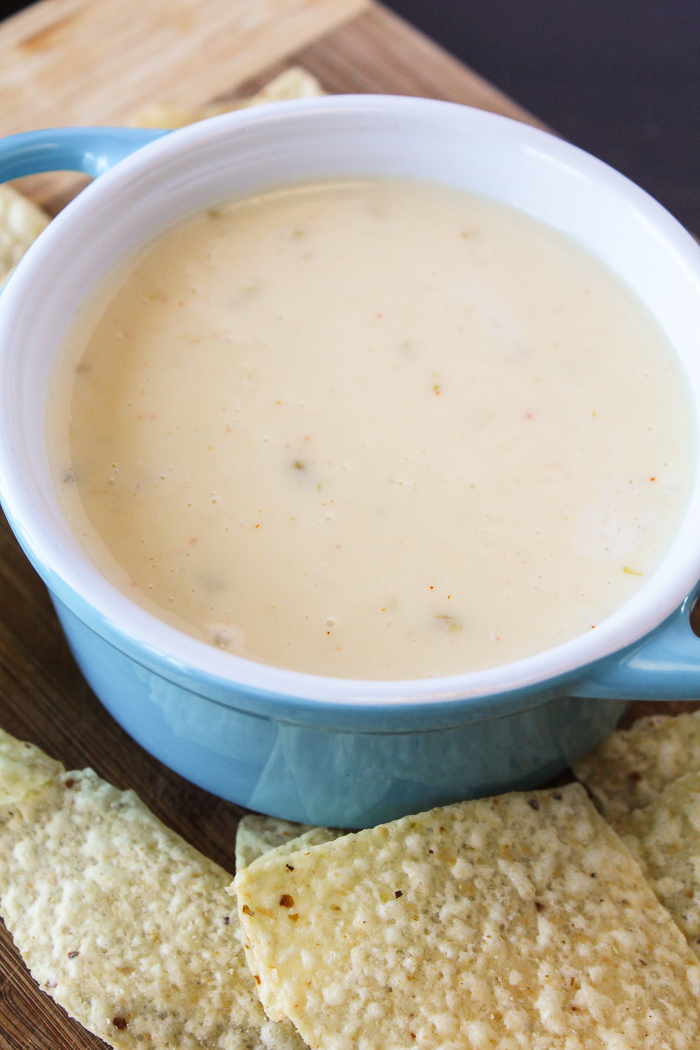 long shot of cheese dip in blue bowl with tortilla chips