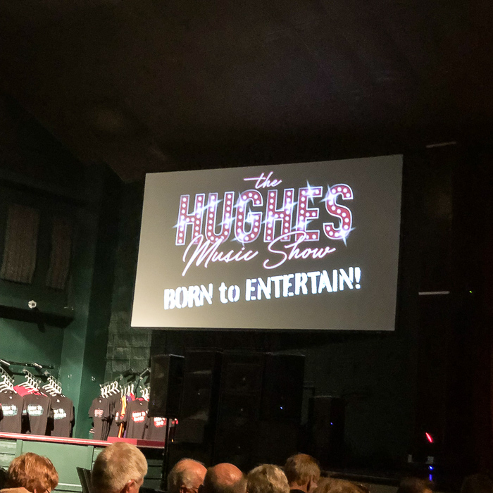 logo and sign for Hughes music show
