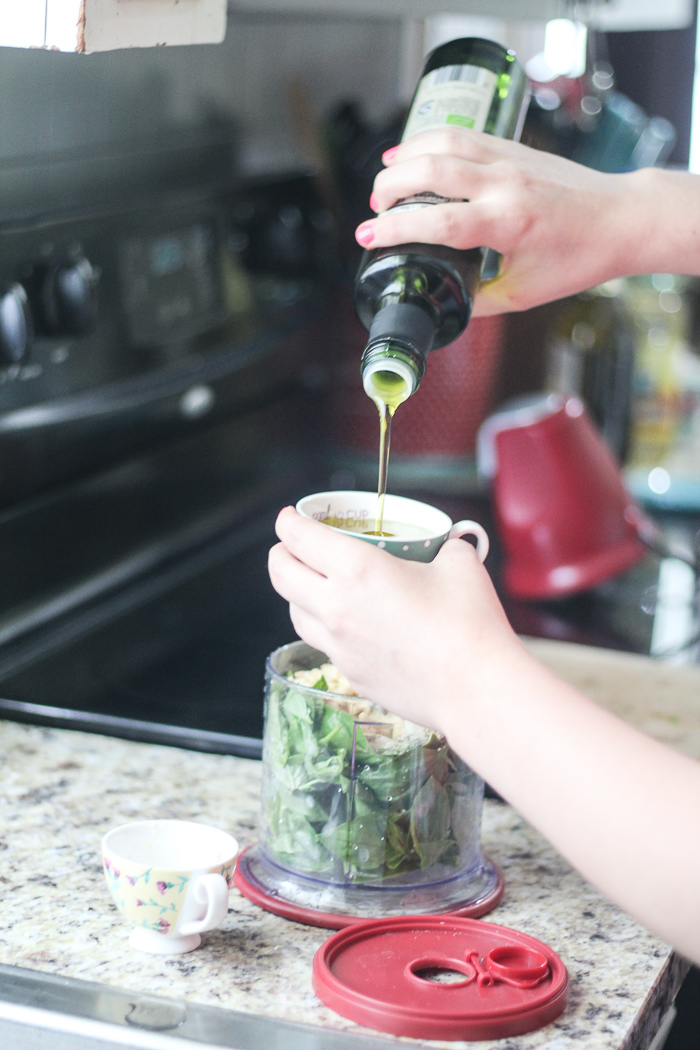 adding olive oil to pesto